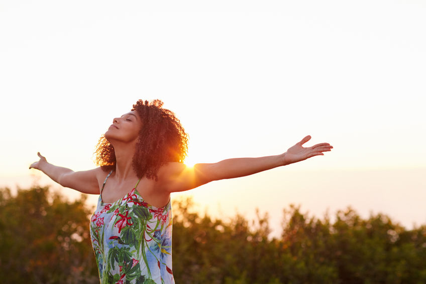 Photo of woman at sunset, with outstretched arms.