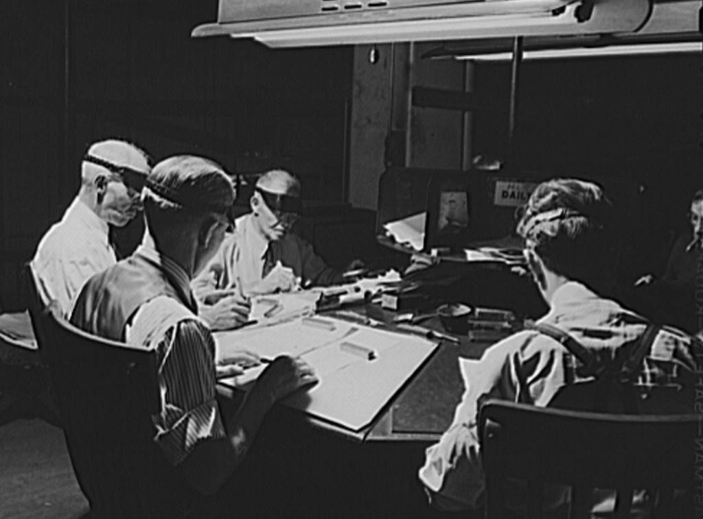 Old black-and-white photo from 1943 showing several older men sitting around a circular desk, intently focused on reading newspaper copy; they are wearing the old-fashioned visors.