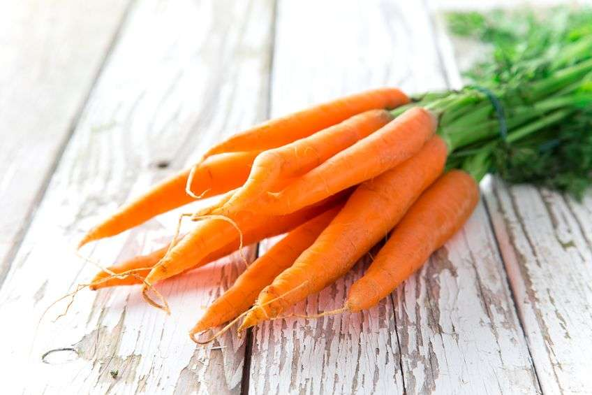 Photo of fresh carrots on a wooden background.