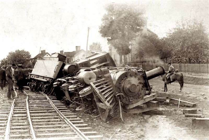 Vintage early 1900s-era photo of old steam train derailed as men gather around on foot and horse to gawk at it.