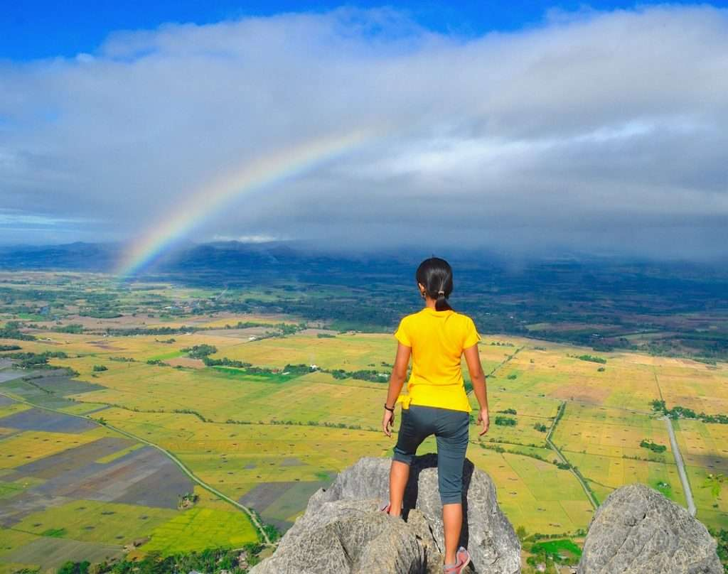 Photo of a girl looking out at a vast landscape from far above, and in the distance there is a rainbow.