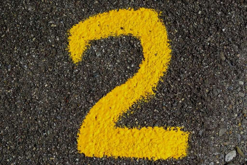 """Photo of a section of road with the number """"2"""" painted in yellow."""
