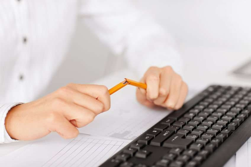 Photo of someone's hands breaking a pencil in frustration near a computer keyboard.