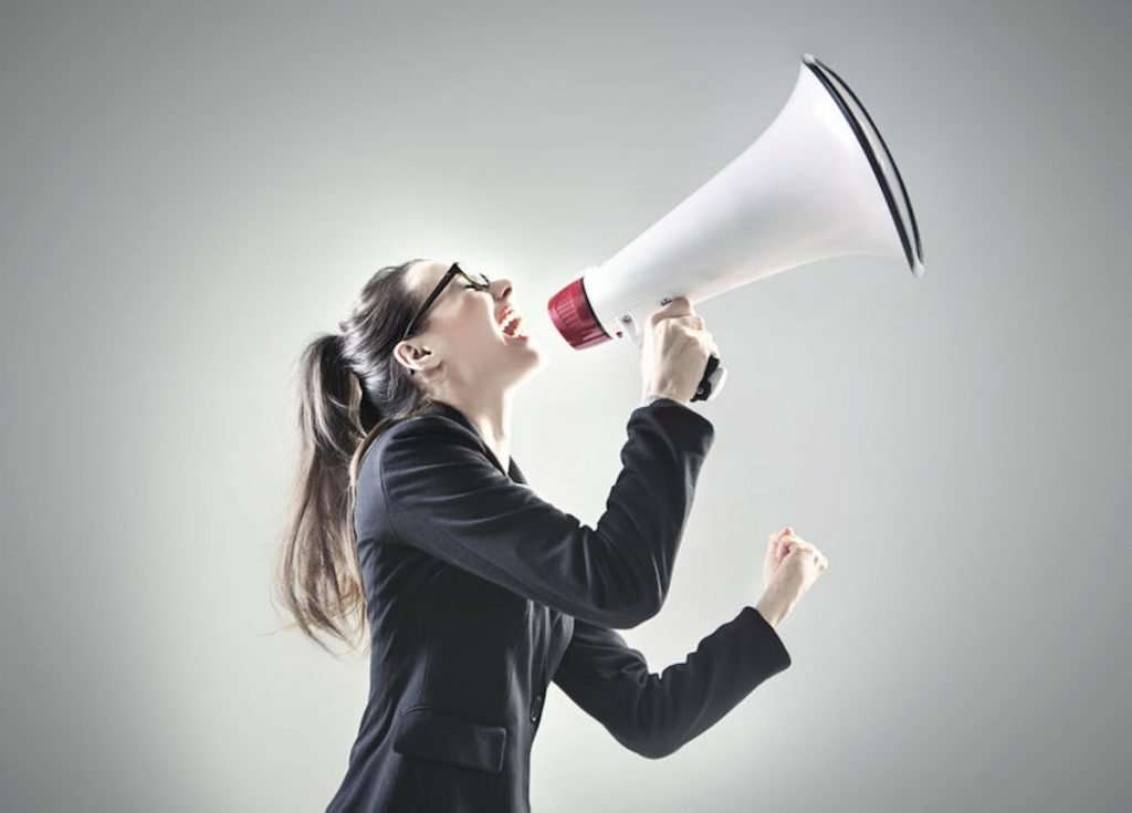 Photo of a woman in a business suit and glasses yelling into a big megaphone.