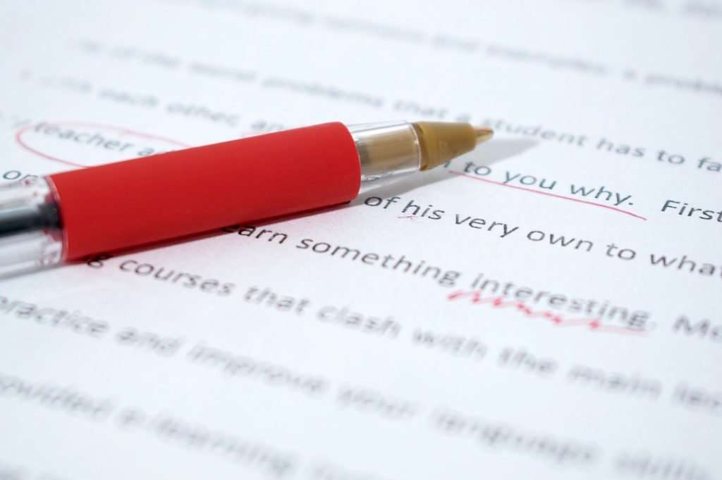 Photo of a red pen on top of a proofreader's marked-up document.