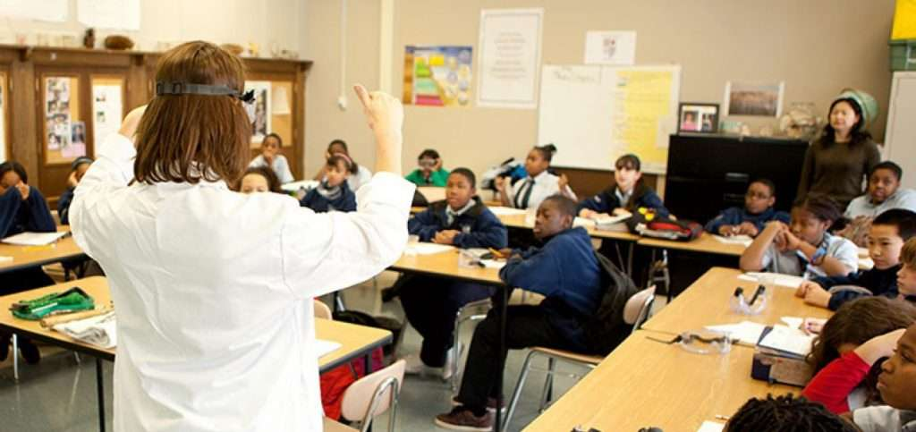 Photo of a teacher with her back to the camera, facing a classroom full of students. She is wearing a white lab coat and has her arms in the air, giving the look of an educator teaching in an exciting way.